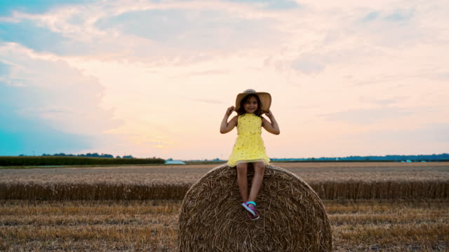 ws girl sitting on hay bale - straw hat stock videos & royalty-free footage