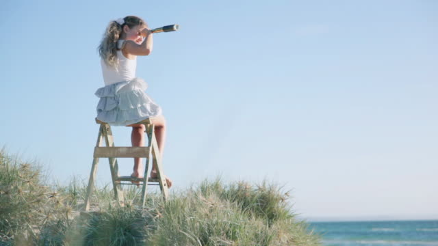 ws girl sitting on ladder looking through telescope at beach / melbourne, victoria, australia - looking through an object stock videos and b-roll footage