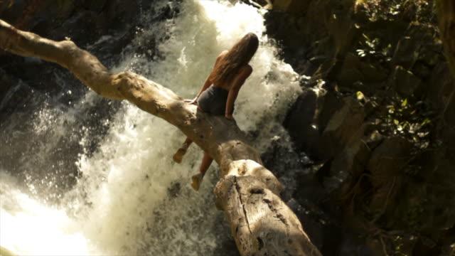 vídeos de stock, filmes e b-roll de menina sentada em log na frente da cachoeira - tronco parte de planta