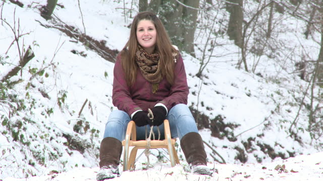 MS girl sitting on sled in winter and after walking out from forest / Saarburg, Rhineland-Palatinate, Germany