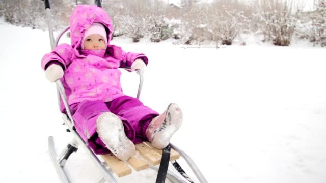 vídeos de stock, filmes e b-roll de menina sentada em trenó - roupa de bebê