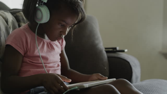 girl sitting on sofa connecting headphones and using digital tablet / orem, utah, united states - concentration stock videos & royalty-free footage
