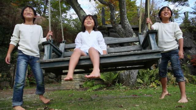 vídeos y material grabado en eventos de stock de ms girl sitting on swing and t children are pushing swing / fujikawaguchiko, yamanashi, japan - columpiarse