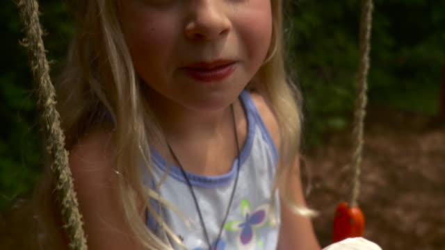 cu tu girl (8-9) sitting on swing eating ice cream cone / stowe, vermont, usa - licking stock videos and b-roll footage
