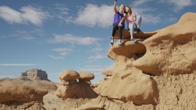 Girl sitting on the edge of rock formation in desert posing for cell phone selfie / Goblin Valley, Utah, United States