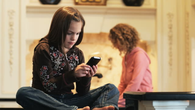 girl sitting on the kitchen counter looking at a cell phone