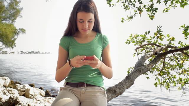 ms girl (14-15) sitting on tree branch by lake and text messaging / cape coral, florida, usa - endast en tonårsflicka bildbanksvideor och videomaterial från bakom kulisserna