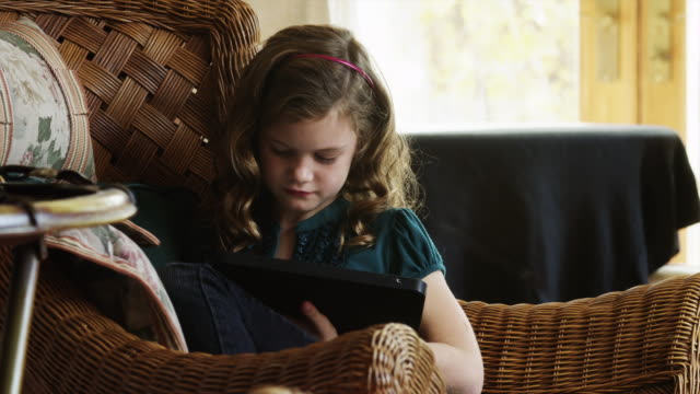 MS ZI Girl (8-9) sitting on wicker armchair and using digital tablet / Cedar Hills, Utah, USA