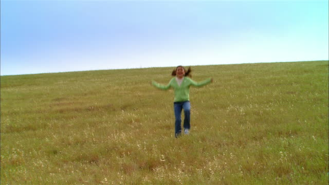 ws girl skipping down grassy hill / livermore, california, usa - skipping along stock videos & royalty-free footage
