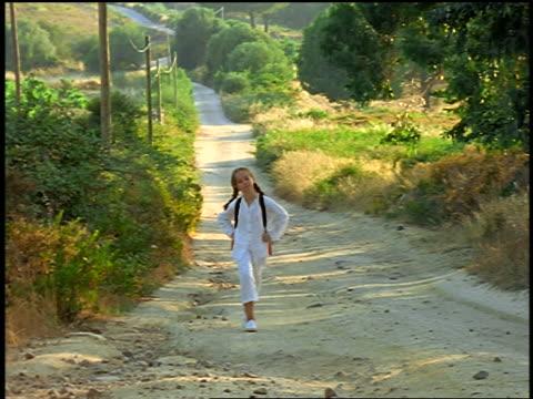 stockvideo's en b-roll-footage met girl skipping on country road toward camera / corsica - alleen meisjes