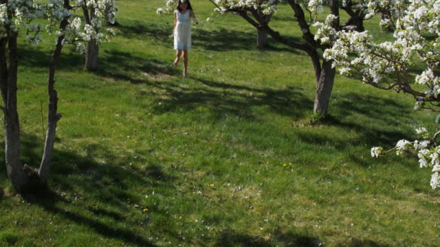 girl skipping through an orchard