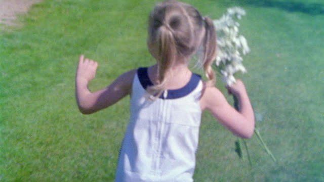 ws slo mo ts girl skipping with bunch of daisies / appleton, wi, usa - appleton video stock e b–roll