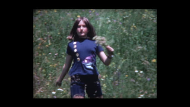 1972 girl skips down hill with bouquet of flowers - field stock videos & royalty-free footage