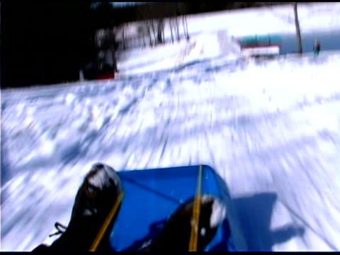 Girl sledding down snowy hill