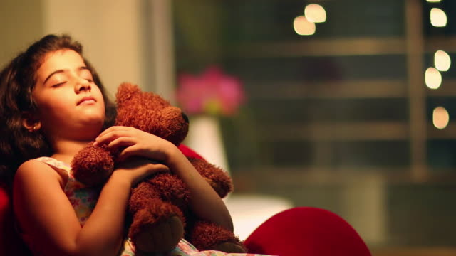 Girl sleeping with a teddy bear at night