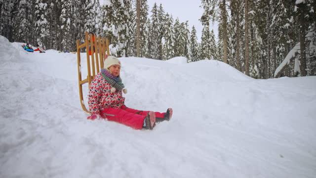 slo mo tsガールは彼女の木製のそりに雪の丘を滑り落ちて、それを落ちる - misfortune点の映像素材/bロール