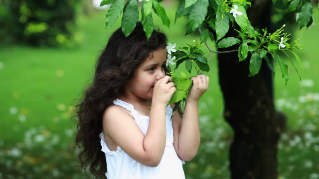 Girl smelling a flower in a garden