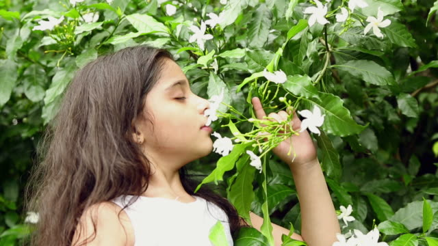 Girl smelling flowers in the garden