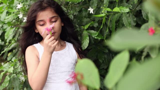 Girl smelling flowers in the garden