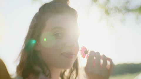 vidéos et rushes de cu slo mo. girl smells flower and looks at camera in open field at magic hour. - sentir