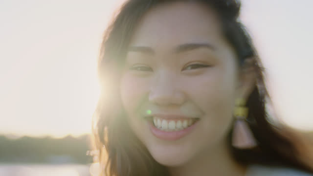cu slo mo. girl smiles at camera with lens flare. - 歯を見せて笑う点の映像素材/bロール