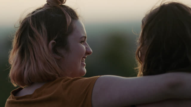 CU SLO MO. Girl smiles with her arm around her sister in open field at sunset.