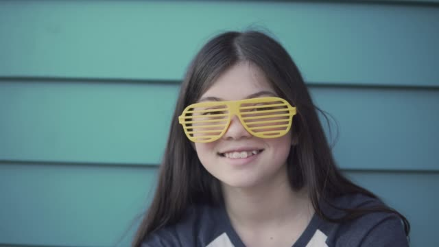 a girl smiling and wearing yellow novelty glasses - pre adolescent child stock videos & royalty-free footage