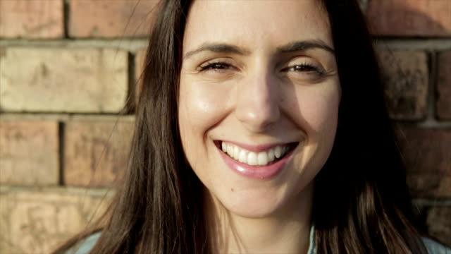 vídeos de stock, filmes e b-roll de menina sorridente no vento-câmera lenta - cabelo assanhado