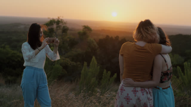 ws slo mo. girl snaps photos of sunset with smartphone and takes pictures of friends on mountainside. - social gathering stock videos & royalty-free footage