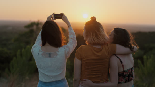 ms slo mo. girl snaps photos of sunset with smartphone as friends hug on scenic mountainside. - photographing stock videos & royalty-free footage