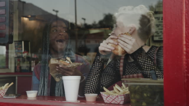 vídeos de stock e filmes b-roll de girl sneaking bite of sandwich of friend in cafe window / provo, utah, united states - surpresa