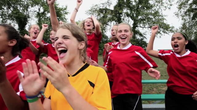 Girl soccer players cheering and clapping