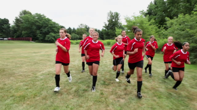 Girl soccer players running in field