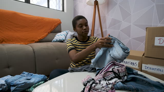 vídeos y material grabado en eventos de stock de chica clasificando ropa para enviarla al servicio social - sólo mujeres jóvenes