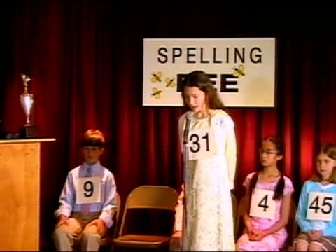 Girl spelling word on stage in spelling bee / Los Angeles, California
