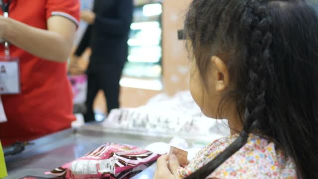 vídeos de stock, filmes e b-roll de menina gastar dinheiro na loja de balcão de caixa - brincadeira de pegar