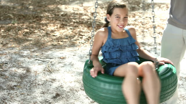 Girl spinning on tire swing in the park