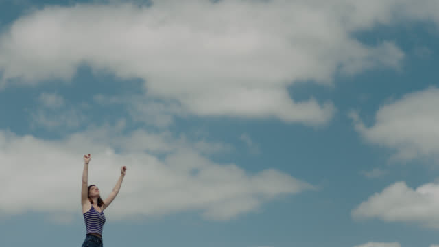 vídeos y material grabado en eventos de stock de ws slo mo. girl spins and claps and holds hands up high against cloudy blue sky. - alzar los brazos