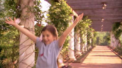 a girl spins and dances in falling flower petals. - blomrabatt bildbanksvideor och videomaterial från bakom kulisserna
