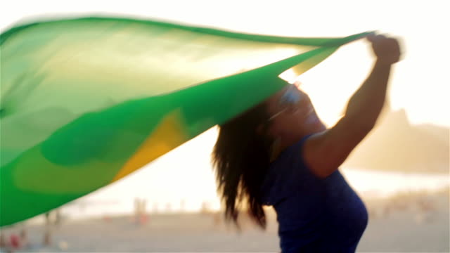 girl spins with brazilian flag on ipanema beach at sunset - waving stock videos & royalty-free footage