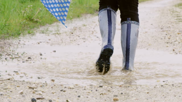 slo mo ms girl splashing a puddle - wellington boot stock videos & royalty-free footage