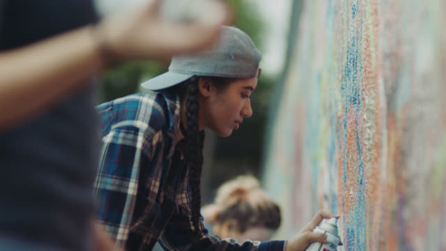 vídeos de stock e filmes b-roll de ms. girl spraypaints graffiti wall with friends. - interatividade