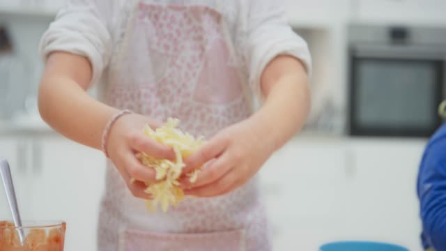 girl spreading grated cheese onto her pizza dough - grated stock videos & royalty-free footage