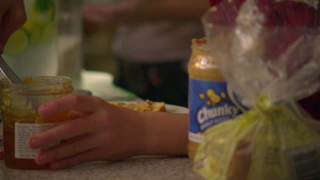 cu selective focus girl (10-11) spreading jam on bread in kitchen,  mother in background, north hollywood, california, usa - サンドイッチ作り点の映像素材/bロール