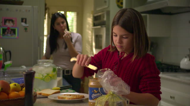 ms girl (10-11) spreading peanut butter on bread in kitchen,  mother in background,, north hollywood, california, usa - peanut food stock videos and b-roll footage