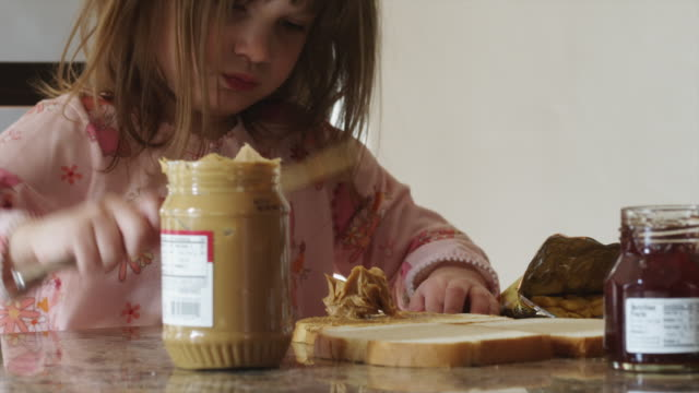 CU Girl (4-5) spreading peanut butter on toast / Cedar Hills, Utah, USA