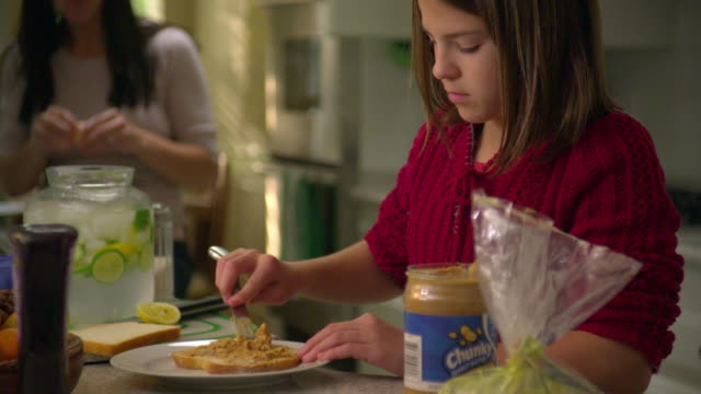 vidéos et rushes de cu girl (10-11) spreading preparing sandwich in kitchen,  mother in background, north hollywood, california, usa - étaler