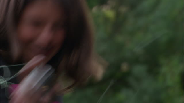 cu, girl (10-11) squirting party strings and laughing outdoors, los angeles, california, usa - squirting girl stock videos and b-roll footage