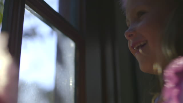 vidéos et rushes de  ecu girl standing and smiling at window to say goodbye to dad / los angeles, california, united states - regarder par la fenêtre