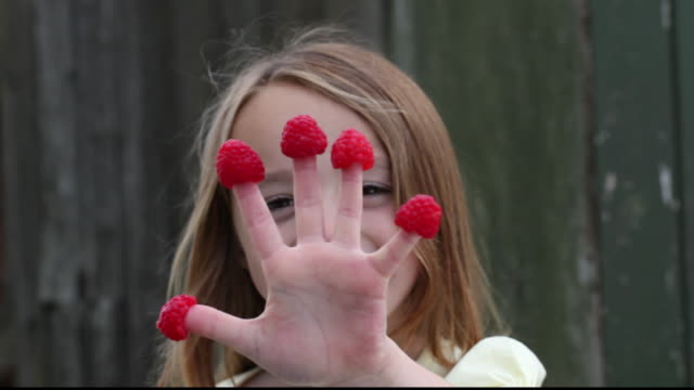 r/f girl standing and smiling with a raspberry on each of her fingers / great yarmouth, england, united kingdom - fruit stock videos & royalty-free footage